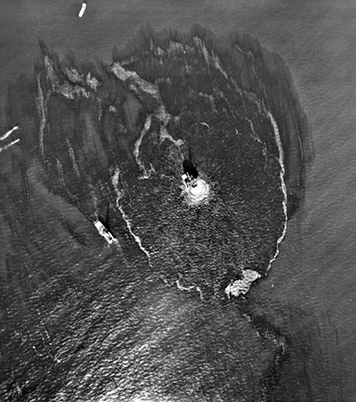 Aerial view of oil platform and response ships, surrounded by oil slicks.