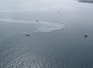 Boats skimming oil off the ocean surface.