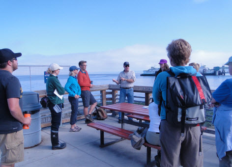 A group of people gathered on a deck, with a ferry in the background.
