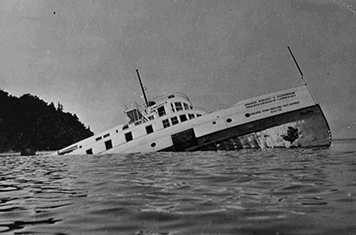 Black and white photo of a steam ship half sinking in the Great Lakes.
