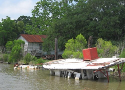 Sunken boat next to a house in Louisiana.