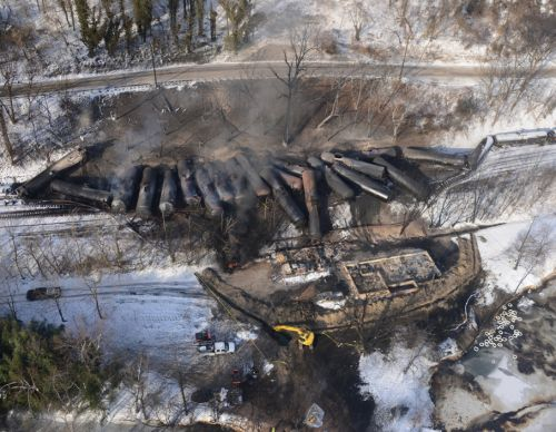Smoldering train cars derailed from the railroad tracks in snowy West Virginia.