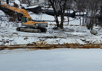Heavy equipment and oily boom on the edge of a frozen river.