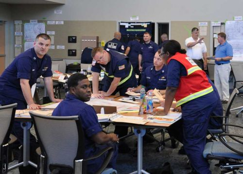 Group of Coast Guard members sit and stand at a table.