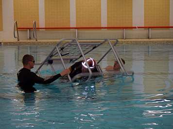 Coast Guard rolling a person in a simulated helicopter chair underwater.