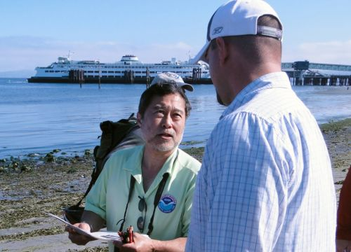 A NOAA spill responder with a clip board talking on a beach with a ferry behind.