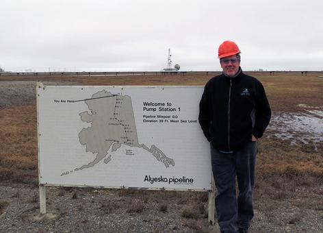 Man in hard hat outside at sign at start of Trans Alaska Pipeline.