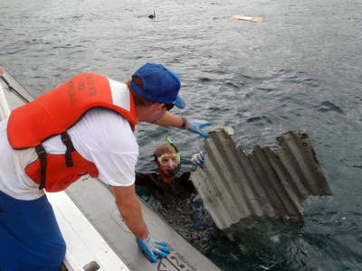 Photo: A diver retrieves a piece of debris from the 2011 Japan tsunami.