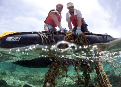 Two people pull a fishing net out of the water into a small boat.