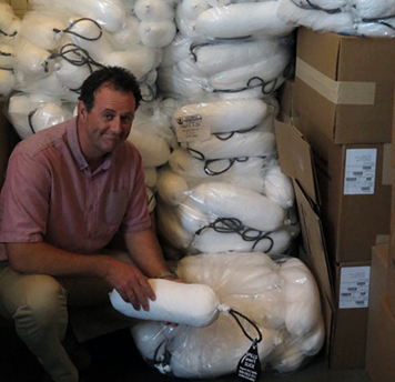 Aaron Barnett holds a bilge sock next to stacks of them.