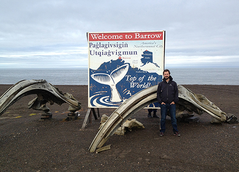 NOAA employee stands with bowhead whale bones and a welcome sign to Barrow.