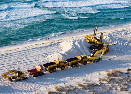Tractor with trailers on beach.