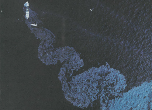 Large oil slick swirl on ocean with ship.
