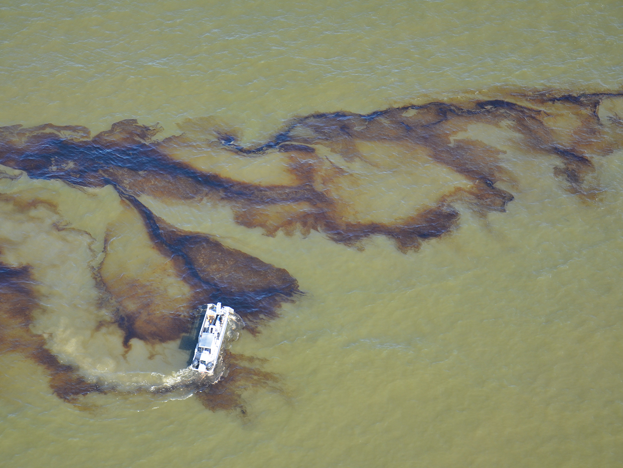 Boat on water near oil spill.