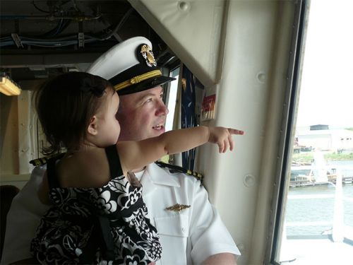 Uniformed man holding little girl.