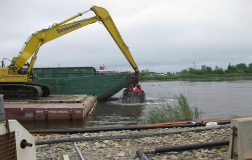 Mechanical shovel scooping mud from river's edge.