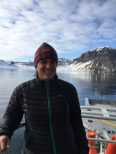 Amy Merten on boat with Arctic ice in background. Image credit: NOAA.
