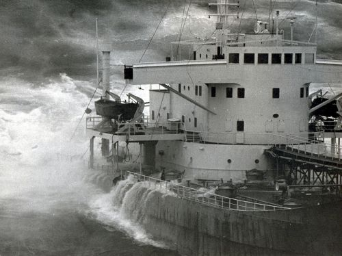 Black and white photo of ship with crashing waves.