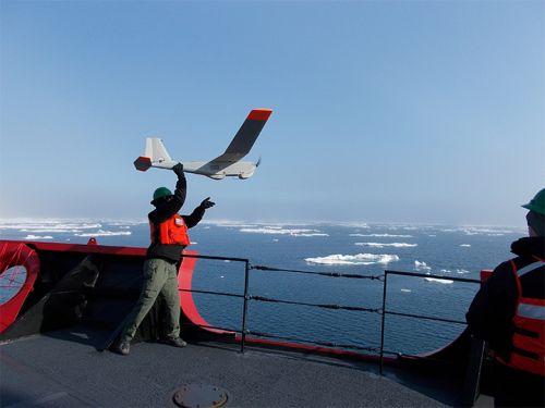 Man on ship holding mini plane.