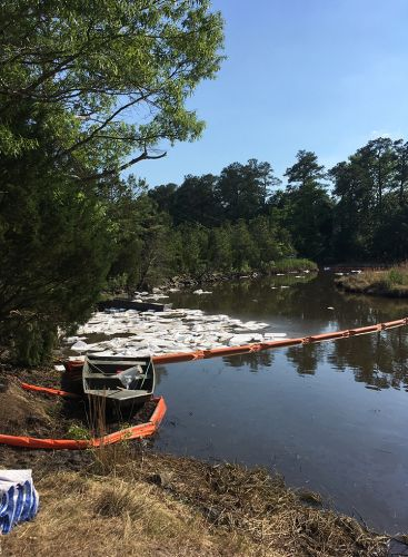 Orange booms across water holding back spill. Image credit: NOAA.