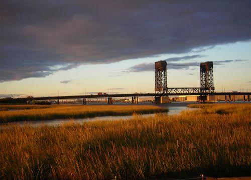 Grass at waterway with bridge at sunset.