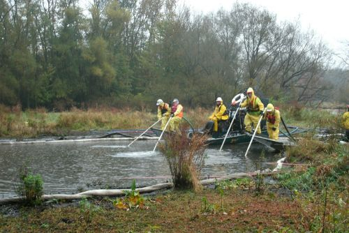People standing in boats on river spraying water with hoses.