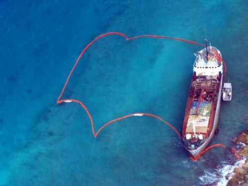 A ship run aground on coral reef, surrounded by protective oil boom.