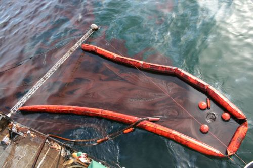 Close up of skimming device on side of a boat with oil and boom.