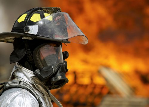 Man in chemical protective mask with fire in background.