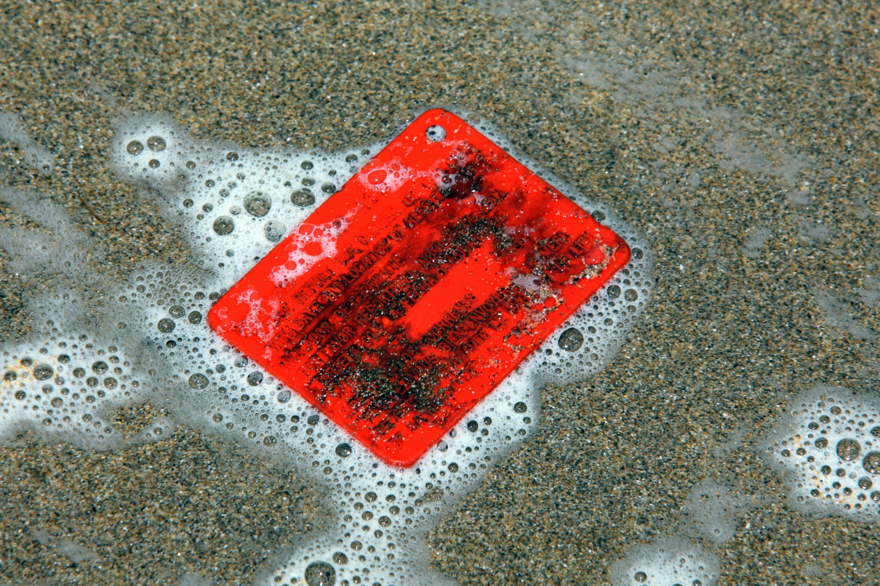 An orange plastic drift card lies in some foam on a beach.