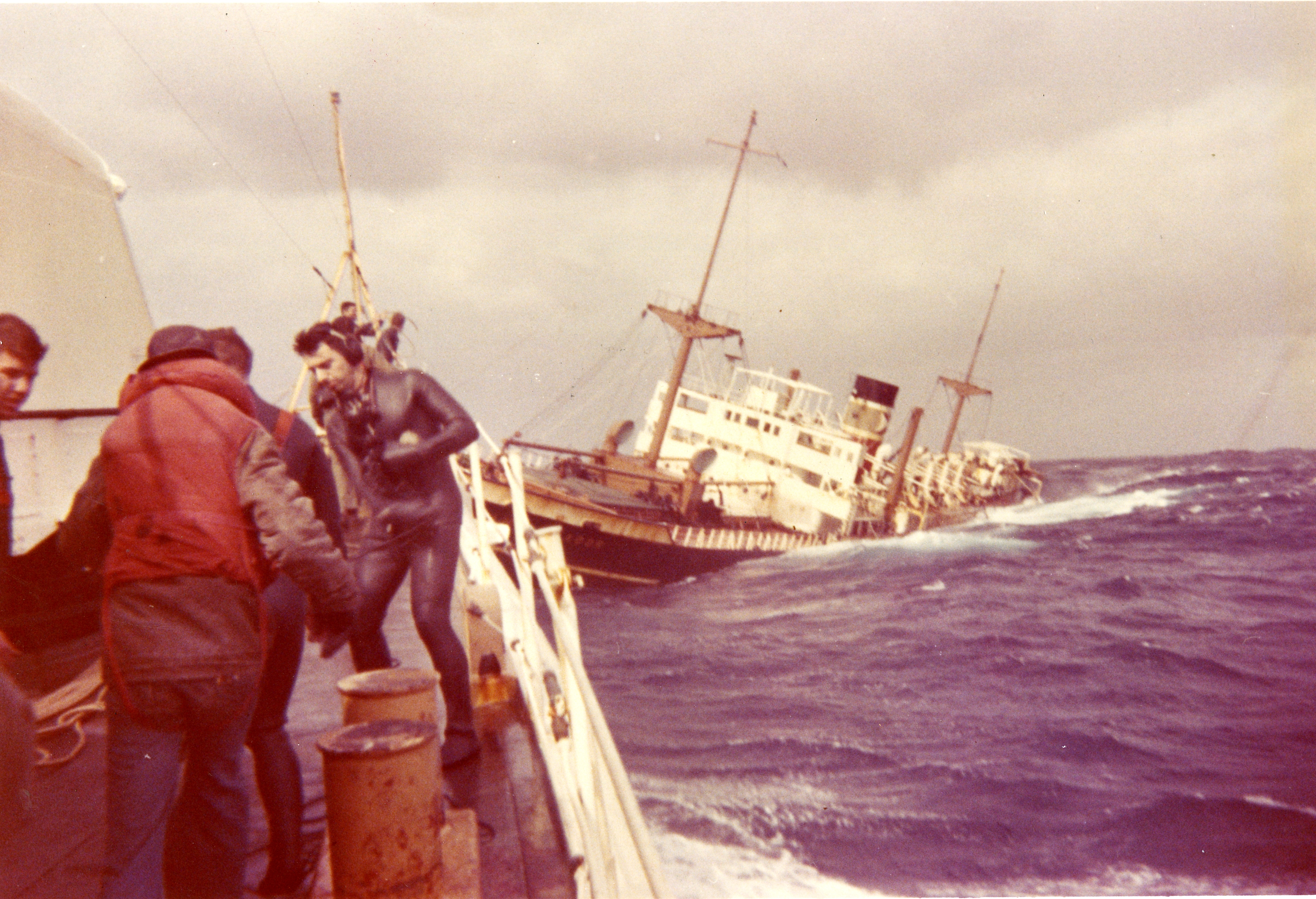 Responders, including one in a wetsuit, work on a vessel next to a sinking ship.