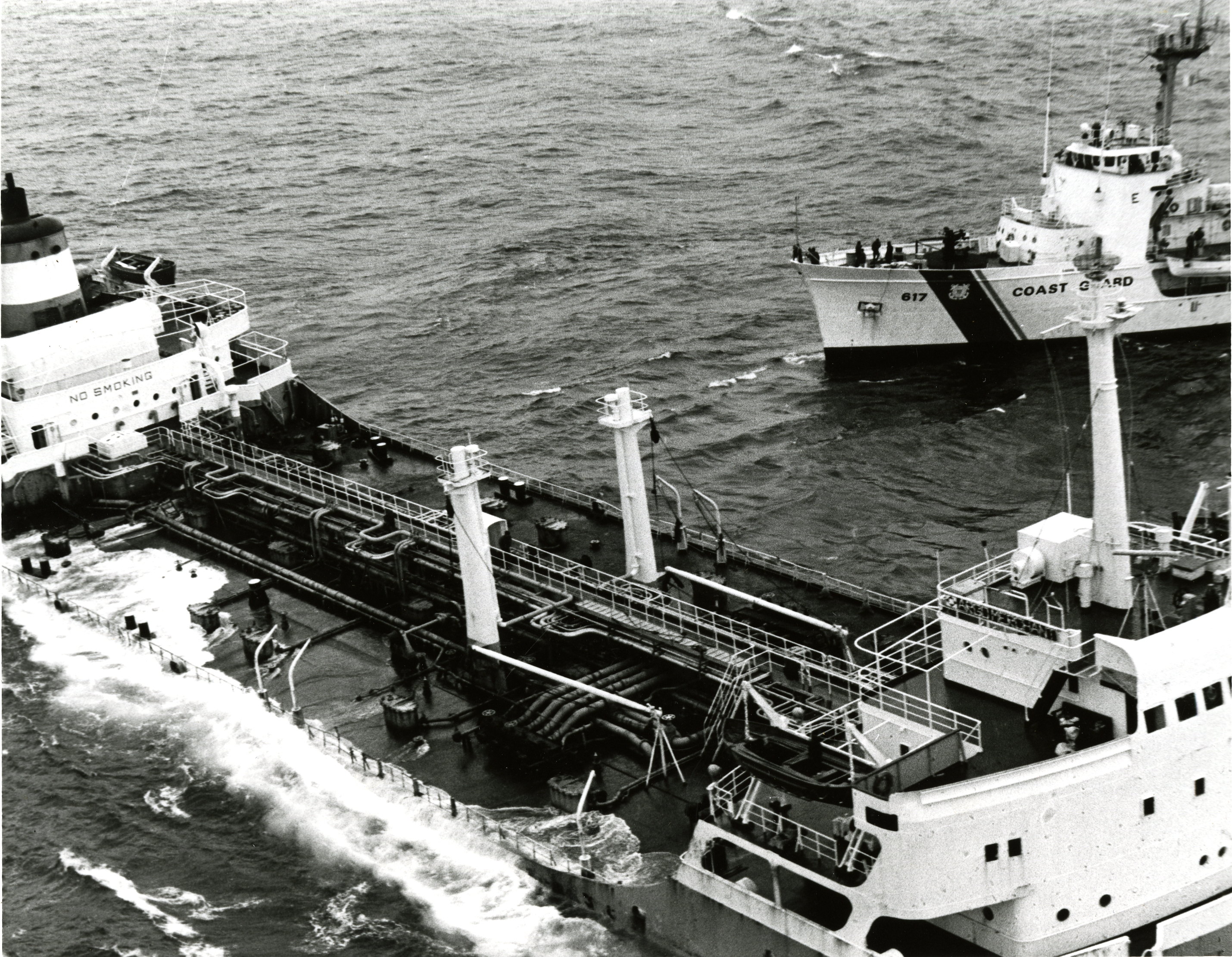 A Coast Guard vessel near a foundering ship.