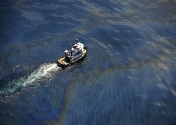 Aerial view of a tug boat crossing oil sheen.