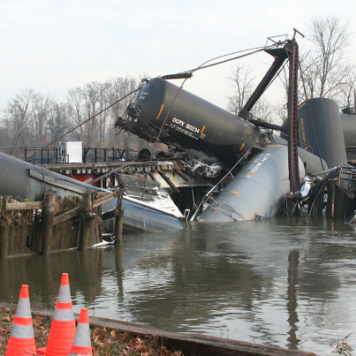 Photo: Several rail cars partially submerged in a creek.