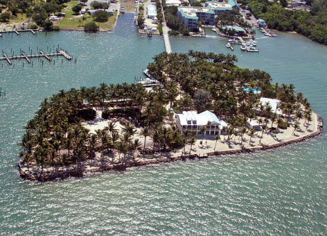 A small island with palm trees, a large home, and a riprap perimeter.