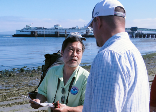 Instructor talks with student on a beach, with ferry in background.