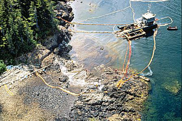 Photo: Aerial shot of maxi-barge and shoreline workers cleaning a beach.
