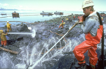 Photo: Cleanup workers spray oil-covered rocks with high-pressure hoses.