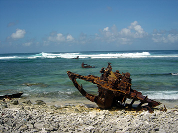 Rusted debris from a grounded vessel sets on the beach and in the surf.