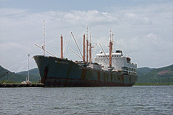 Large rusting vessel in harbour.