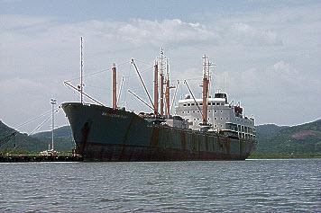 Large rusting vessel in harbour.