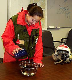 A student pours oil into a bowl of water.