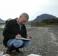 A spill responder on a gravel beach, making hand-written notes.