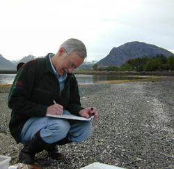 A spill responder on a gravel beach, making hand-written notes.