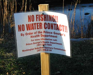 Photo: A sign warning the public not to have contact with the river.