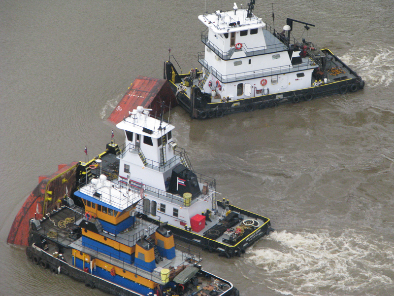 Tugs respond to the submerged Barge DM932.