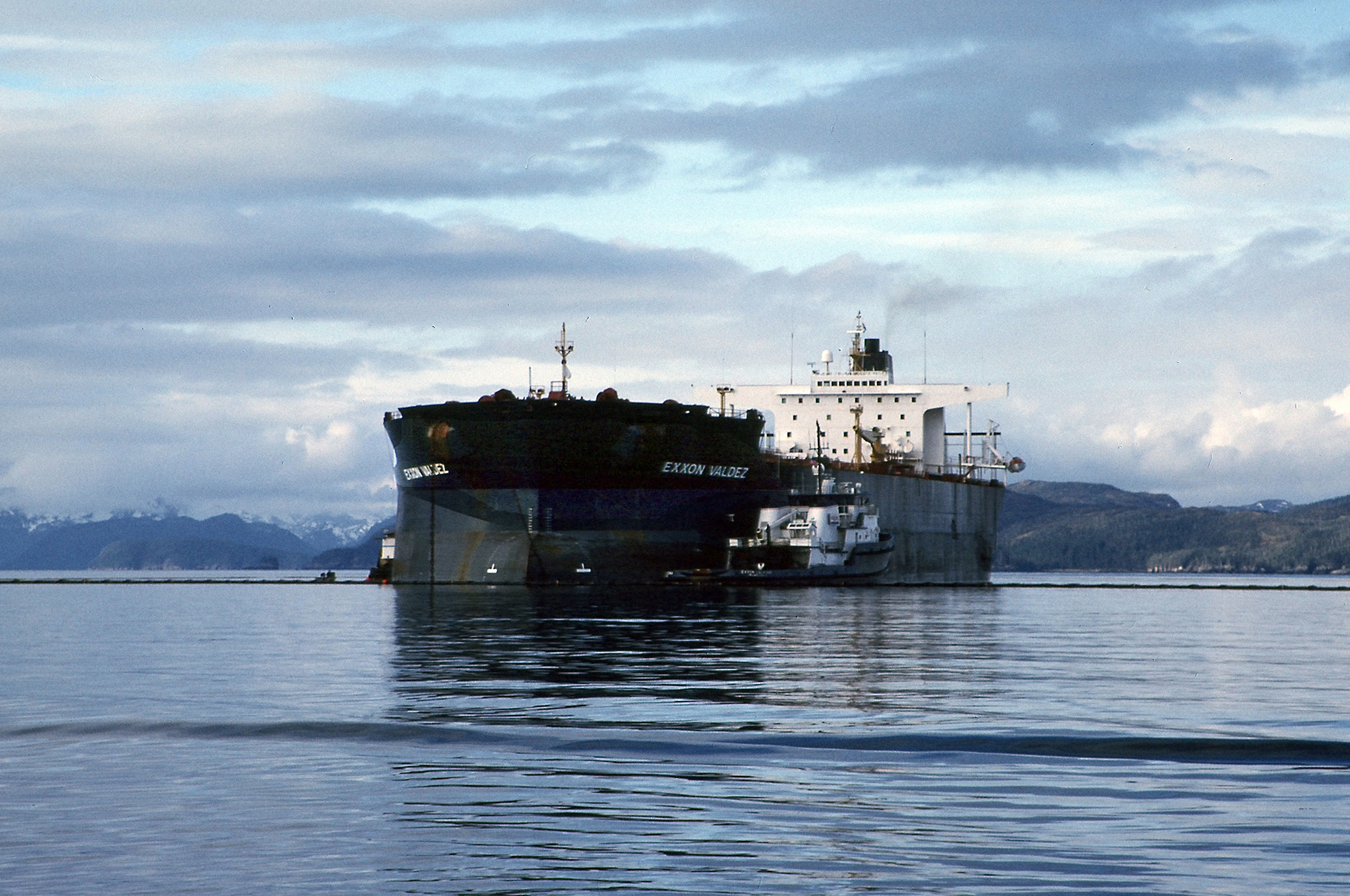 The Exxon Valdez aground; tug assisting in response.