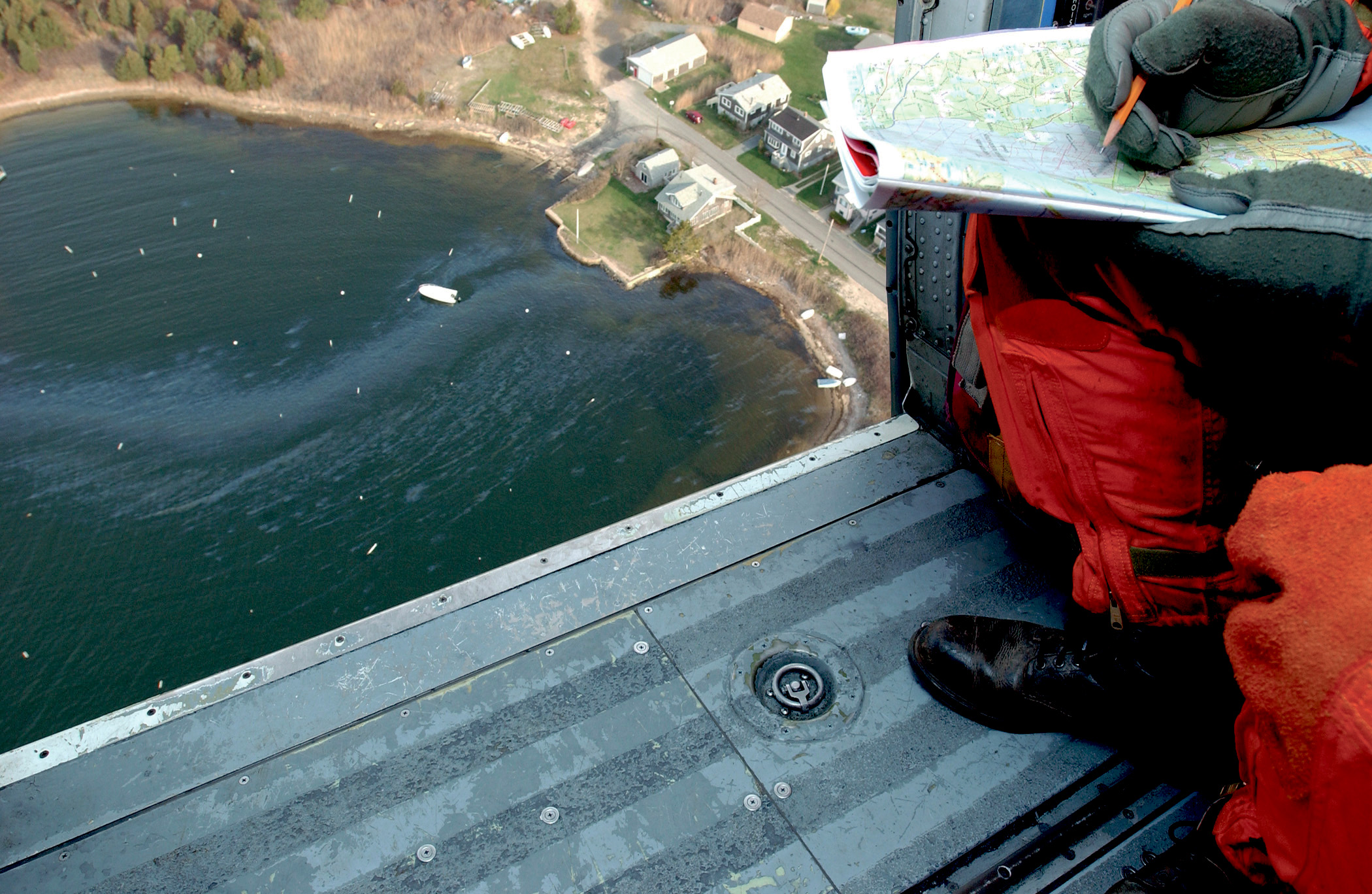 Man in helicopter looking down to oiled shoreline.