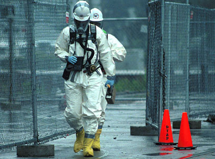 Two emergency responders in protective clothing walk past a fenced area.