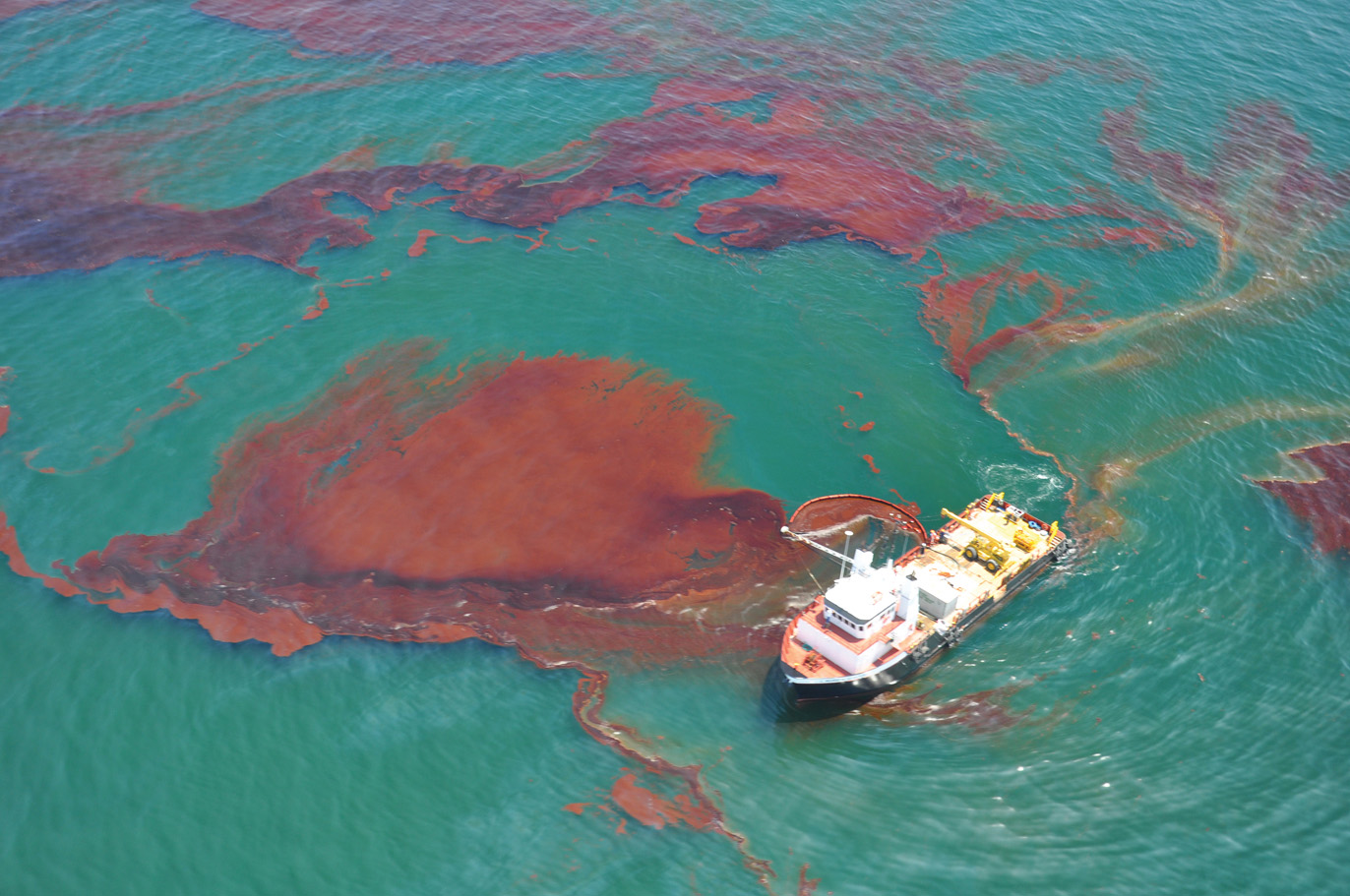 Ship using a skimmer to collect spilled oil.